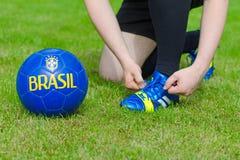 Football player tying his shoes. Brazilian Football Confederation. Football player tying his shoes Stock Photo