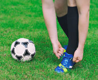 Football player tying his shoes. Football player tying his shoes on the field Stock Photography