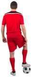Football player wearing red gear standing with ball Royalty Free Stock Photography