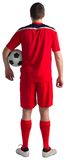 Football player wearing red gear standing with ball Stock Photo