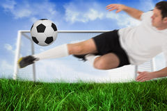 Football player in white kicking ball Stock Images