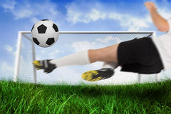Football player in white kicking the ball Royalty Free Stock Photos
