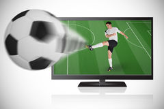 Football player in white kicking ball out of tv Royalty Free Stock Photo