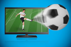 Football player in white kicking ball out of tv Royalty Free Stock Image