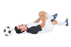 Football player in white lying injured Stock Images