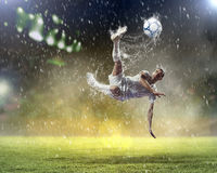 Football player striking the ball. Football player in white shirt striking the ball at the stadium under the rain royalty free stock image