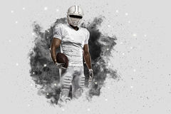 Football Player. With a White uniform coming out of a blast of smoke stock photo