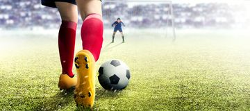 Football Player Woman In Orange Jersey Kicking The Ball In The Penalty Box Stock Photo