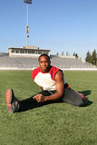 Football Player Workout. A strong football player stretching before the game Stock Photos
