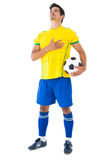 Football player in yellow with ball listening to anthem Stock Photo
