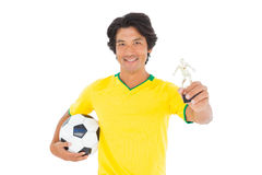 Football player in yellow holding winners trophy Stock Photos