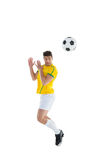 Football player in yellow jersey jumping to ball Royalty Free Stock Image
