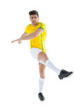 Football player in yellow jersey kicking Stock Image
