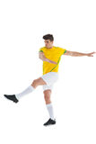 Football player in yellow jersey kicking Stock Photos