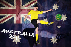 Football player in yellow kicking Stock Photos