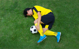 Football player in Yellow lying injured on the pitch. Top View Football player in Yellow lying injured on the pitch Stock Image