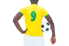 Football player in yellow standing with the ball Stock Image