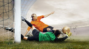 Football players. Shoot of football player and jump of goalkeeper on the field of stadium Royalty Free Stock Photo