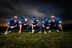 Football Players in Blue Jersey Lined Under Grey White Cloudy Sky during Sunset Royalty Free Stock Photography