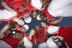 Football Players And Cheerleaders In Huddle. View from below of football players and cheerleaders in huddle against clear sky Royalty Free Stock Photo