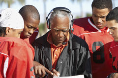 Football Players And Coach Discussing Strategy. Together stock photo