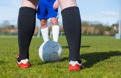 Football players facing off on pitch Stock Photography