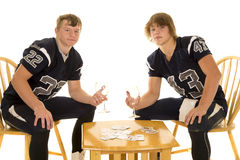 Football players with playing cards looking Stock Images