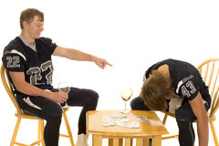 Football players with playing cards one pointing laughing Stock Images
