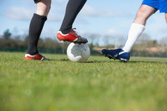 Football players tacakling for the ball on pitch Stock Photos