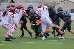 Tackle At A High School Football Game. Football players tackle each other as they try and regain the ball royalty free stock image