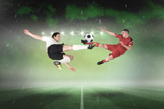 Football players tackling for the ball Royalty Free Stock Photo