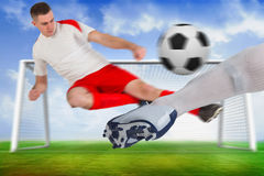 Football players tackling for the ball Royalty Free Stock Image