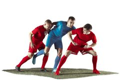 Football players tackling for the ball over white background. Professional football soccer players in motion isolated white studio background. Fit jumping Stock Image