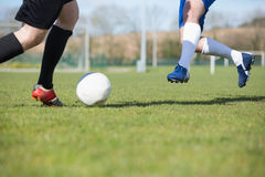 Football players tackling for the ball on pitch Stock Image