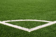 Football playground corner on artificial green turf ground with painted white line marks. Milled black rubber in basic. Stock Images