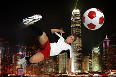Football power. Young footbal player in a acrobatic pose kicking a ball iwith night citys lights in the background Royalty Free Stock Photos