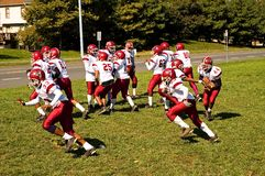 Football Practice. A squad of youth league football players practice a running play to get ready for the big game Royalty Free Stock Photos