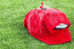 Football practice uniform with full pads ready for action. A red practice uniform over full pads is ready to be put on by a high school football player for Royalty Free Stock Images