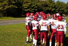 Football Pre-game Pep Talk - 3. Players huddle with their coach as they prepare for their youth league football game on a bright autumn morning Royalty Free Stock Image