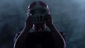 Football puts the helmet on the head in the smoke. Slow motion. Football player puts his helmet on his head in the smoke. Black background. Slow motion stock video