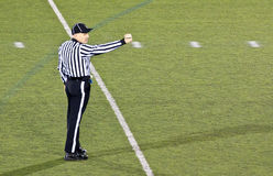 Football Referee Making A Signal. A football referee making a hand signal at a high school football game stock image