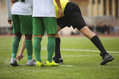 Football Referee marks kick off positions Stock Image