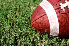 Football resting on field. Angled view of resting football laying on grassy field Royalty Free Stock Photo