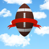 Football with ribbon flying in the sky. Royalty Free Stock Images