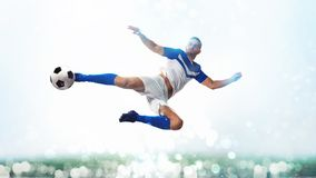 Soccer striker hits the ball with an acrobatic kick in the air on white background. Football scene with a player who kicks the ball on the fly at the stadium royalty free stock photo