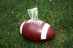 Football Scholarship & Sponsorship. A football money bank stuffed with money represents a college scholarship Stock Photography