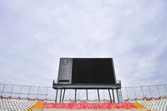 Football scoreboard and empty tribune. Football scoreboard with clock and empty tribune with overcast sky on background Stock Photo