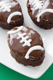 Football shape brownies. Homemade football shaped brownies covered with dark chocolate frosting with white piping. Shallow DOF Royalty Free Stock Images