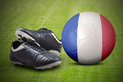 Football shoes and ball at field Royalty Free Stock Image