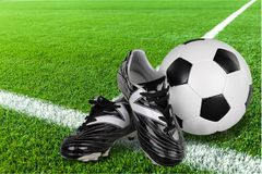 Football shoes and ball on green field. Game sport leisure white objects background ball Royalty Free Stock Image